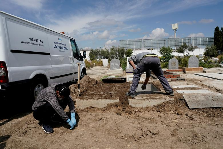 A relative of a person who died of coronavirus reacts as a funerary worker closes the grave at the Spanish Muslim military cemetery during a burial in Grinon, Spain, April 8. REUTERS/Juan Medina