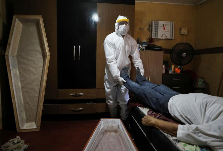 A worker of the Funeral SOS, wearing protective clothing, prepares to remove the body of Antonio Freitas, at his house at Tancredo Neves neighborhood in Manaus, Brazil May 7. REUTERS/Bruno Kelly