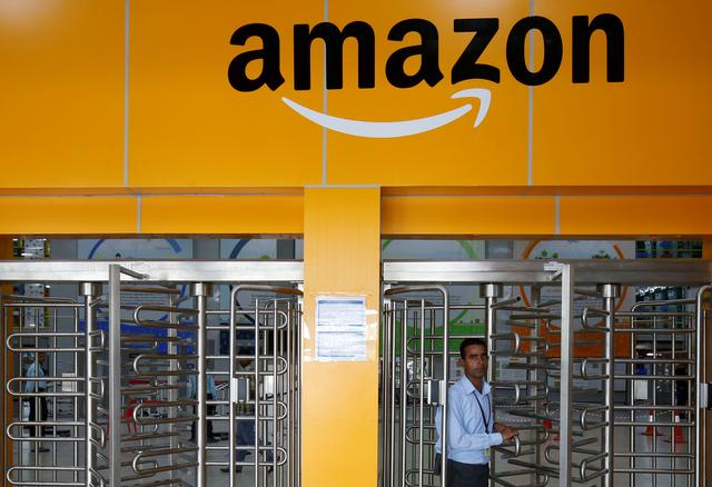 FILE PHOTO: An employee of Amazon walks through a turnstile gate inside an Amazon Fulfillment Centre on the outskirts of Bengaluru, India, September 18, 2018. REUTERS/ Abhishek N. Chinnappa/File Photo