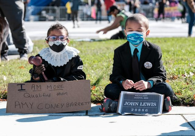 Children dressed up as Justice Ruth Bader Ginsburg and John Lewis sit, as Women's March activists participate in a nationwide protest against U.S. President Donald Trump's decision to fill the seat on the Supreme Court left by the late Justice Ruth Bader Ginsburg before the 2020 election, in Washington, U.S., October 17, 2020. REUTERS/Michael A. McCoy