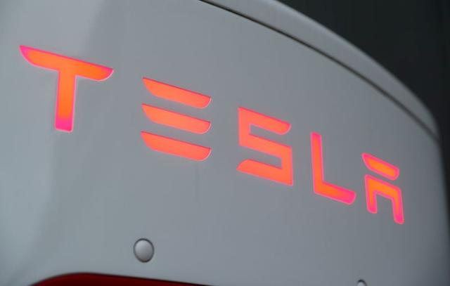 FILE PHOTO: The logo of Tesla is seen at a Tesla Supercharger station in Dietikon, Switzerland October 21, 2020. REUTERS/Arnd Wiegmann