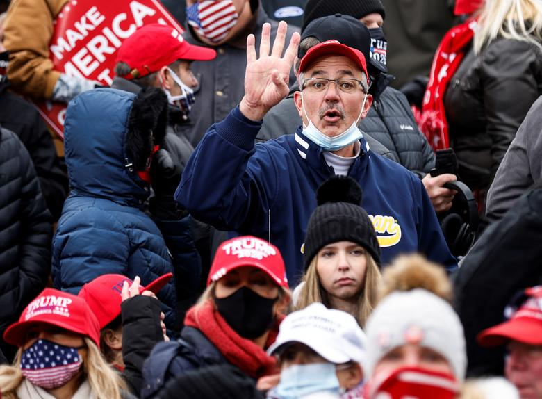 A Trump supporter gestures four more years as President Trump holds a campaign rally at Oakland County International Airport in Waterford Township, Michigan, October 30. REUTERS/Carlos Barria