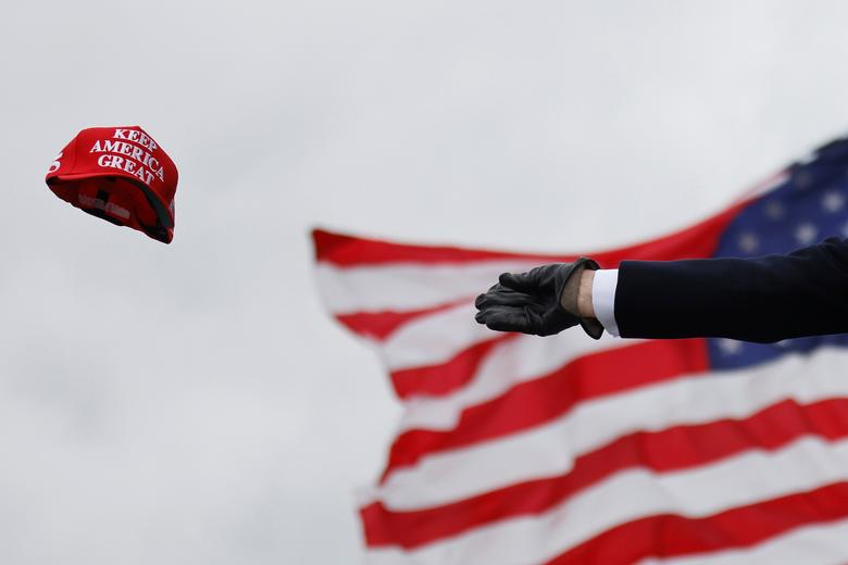 President Trump tosses out MAGA caps as he arrives for a campaign rally at Oakland County International Airport in Waterford Township, Michigan, October 30. REUTERS/Carlos Barria