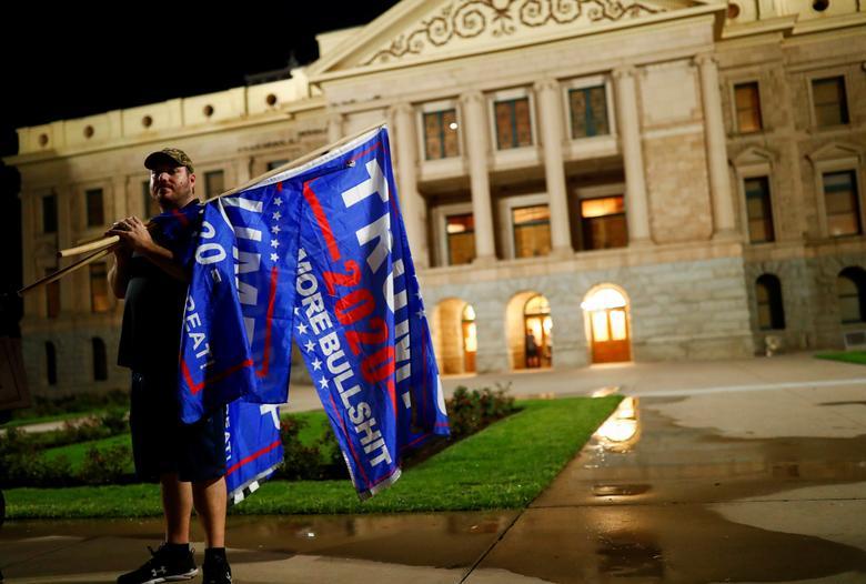 Donald Trump'ın bir destekçisi, 4 Kasım 2020'de Phoenix, Arizona'da 2020 başkanlık seçimlerinin erken sonuçlarını protesto etmek için Arizona Eyaleti Meclis Binası önünde dururken bayrak taşıyor. REUTERS / Edgard Garrido