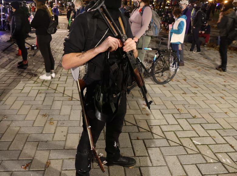 4 Kasım 2020, Portland, Oregon'da bir protesto sırasında bir gösterici banjo taşıyor ve Sırp yapımı AK-47 tüfeği. REUTERS / Goran Tomasevic