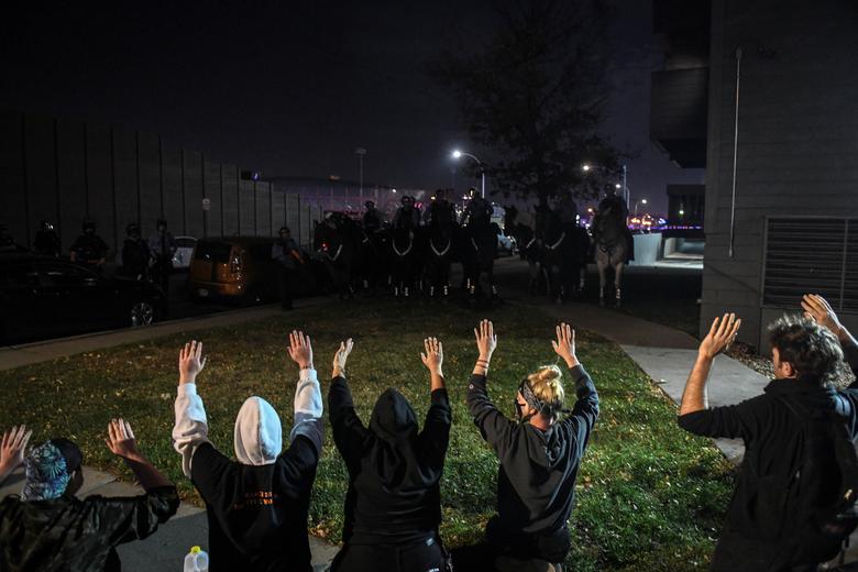 Protestocular, 4 Kasım 2020 Minneapolis, Minnesota'daki Seçim Günü'nün ertesi günü Interstate 94 (I-94) yanındaki bir apartman kompleksinin önünde atlı polis memurlarıyla karşı karşıya geliyor. REUTERS / Nicholas Pfosi