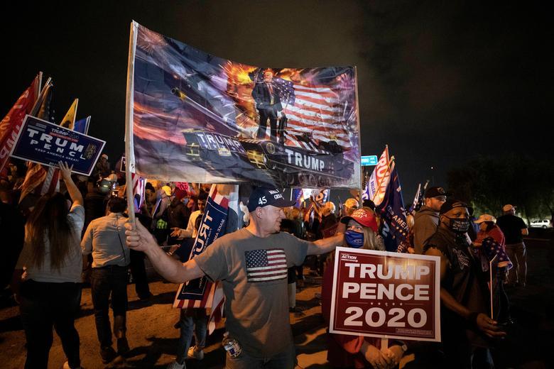 """Başkan Trump'ın destekçileri Doug ve Barbara Remeta, Nevada'nın North Las Vegas kentindeki Clark County Seçim Merkezi'nde düzenlenen """"Çalmayı Durdurun"""" protestosu sırasında bir pankart ve bir levha tutuyor, 5 Kasım. REUTERS / Steve Marcus"""