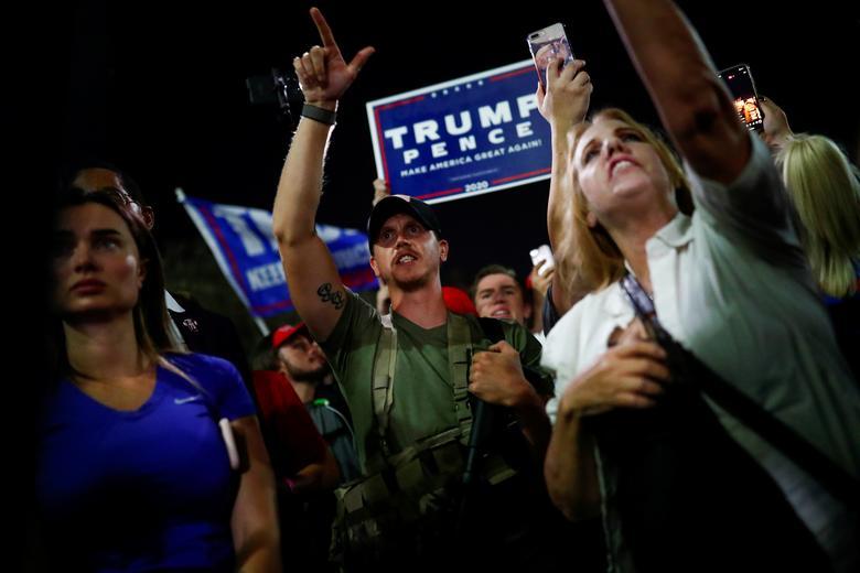 Donald Trump'ın bir destekçisi, 4 Kasım 2020, Phoenix, Arizona'daki Maricopa İlçe Tabulasyon ve Seçim Merkezi (MCTEC) önünde seçimin erken sonuçlarıyla ilgili bir protesto sırasında jest yapıyor. REUTERS / Edgard Garrido