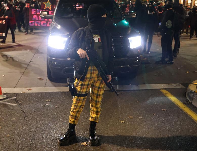 Bir kadın gösterici, 4 Kasım 2020 Portland, Oregon'daki Seçim Günü'nün ertesi günü bir protesto sırasında silah taşıyor. REUTERS / Goran Tomasevic