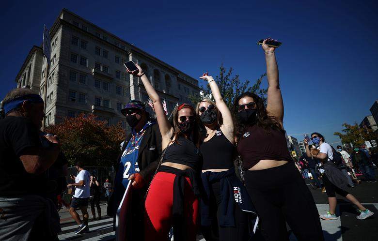 People react as media announce that Joe Biden has won the election, on Black Lives Matter Plaza in Washington, November 7. REUTERS/Hannah McKay