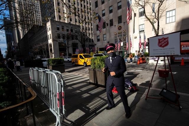 A Salvation Army member wearing a protective mask sings and dances at Rockefeller Center as the spread of the coronavirus disease (COVID-19) continues, in New York City, New York, U.S., November 21, 2020. REUTERS/Jeenah Moon