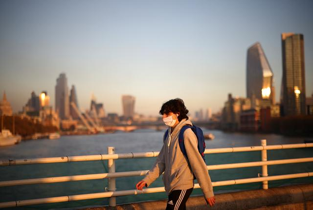 FILE PHOTO: A man wearing a protective face mask walks over Waterloo Bridge during sunset, amid the coronavirus disease (COVID-19) outbreak, in London, Britain, November 5, 2020. REUTERS/Henry Nicholls