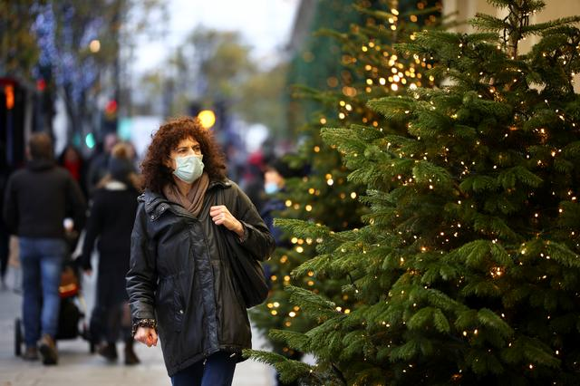 A woman walks past Christmas trees on Oxford Street, amid the coronavirus disease (COVID-19) outbreak, in London, Britain, November 21, 2020. REUTERS/Henry Nicholls