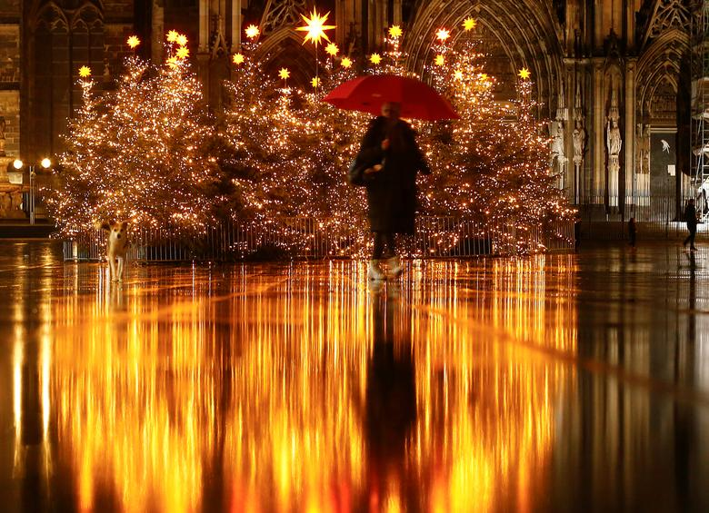A woman walks on a square decorated with Christmas trees in front of the famous Cologne cathedral during lockdown in Cologne, Germany, December 21, 2020. REUTERS/Thilo Schmuelgen