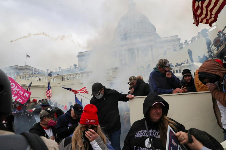 Supporters of President Trump cover their faces from tear gas during a clash with police officers in front of the Capitol Building, January 6. REUTERS/Leah Millis