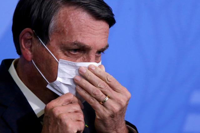 FILE PHOTO: Brazil President Jair Bolsonaro looks on as he adjusts his protective face mask during a ceremony launching a program to expand access to credit at the Planalto Palace in Brasilia, Brazil, August 19, 2020. REUTERS/Adriano Machado//File Photo