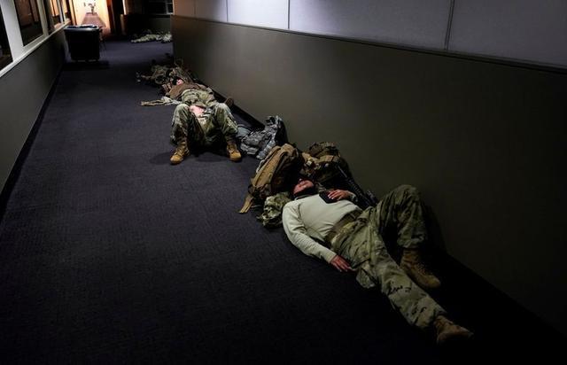 National Guard members sleep in the Dirksen Senate Office Building before Democrats begin debating one article of impeachment against President Trump at the U.S. Capitol, January 13, 2021. REUTERS/Joshua Roberts