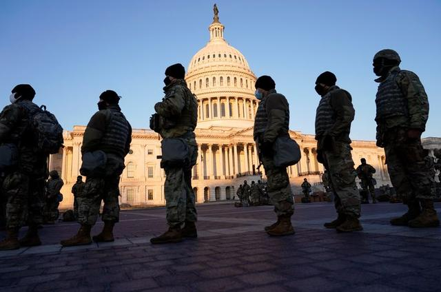 Members of the National Guard are given weapons before Democrats begin debating one article of impeachment against U.S. President Donald Trump at the U.S. Capitol, in Washington, U.S., January 13, 2021. REUTERS/Joshua Roberts