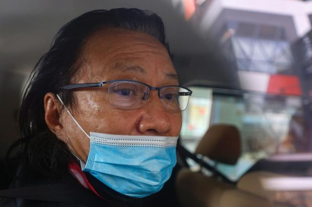 Daniel Wong Kwok-tung, a lawyer who tried to help the 12 people detained in mainland China, is seen inside a police vehicle in Hong Kong, China, January 14, 2021. REUTERS/Tyrone Siu
