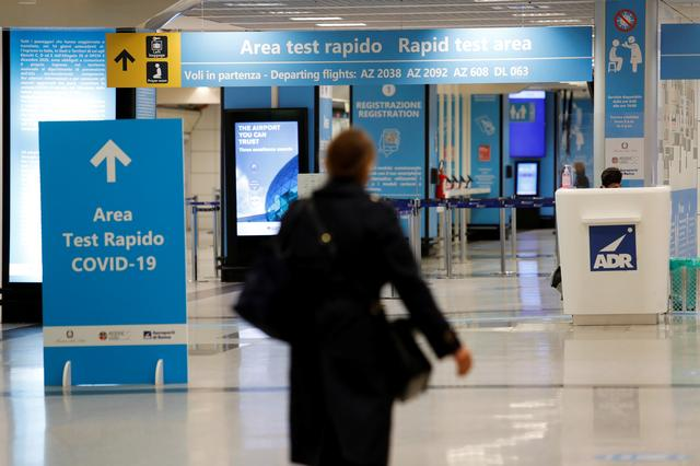 FILE PHOTO: A person walks near of a COVID-19 test area at Fiumicino airport after the Italian government announced flights to and from the UK will be resumed following an order by the Health Ministry, amid the spread of the coronavirus disease (COVID-19), in Rome, Italy, December 24, 2020. REUTERS/Remo Casilli/File Photo