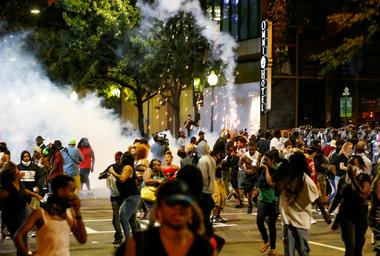 FILE PHOTO: People run from flash-bang grenades in uptown Charlotte, NC...
