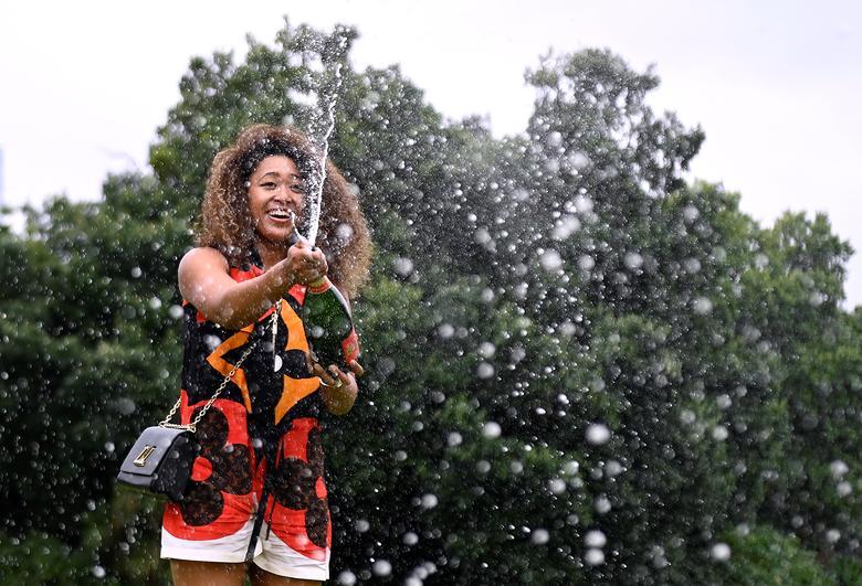 Naomi Osaka celebrates with champagne during a photo shoot at the Royal Botanic Gardens Victoria.REUTERS/Jaimi Joy