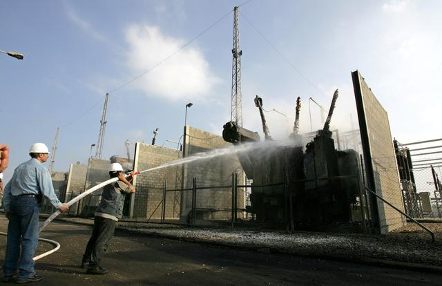 FILE PHOTO: Palestinian electricity workers extinguish a fire inside Gaza's lone power plant which was destroyed by Israeli airstrikes in central Gaza Strip June 28, 2006. REUTERS/Mohammed Salem
