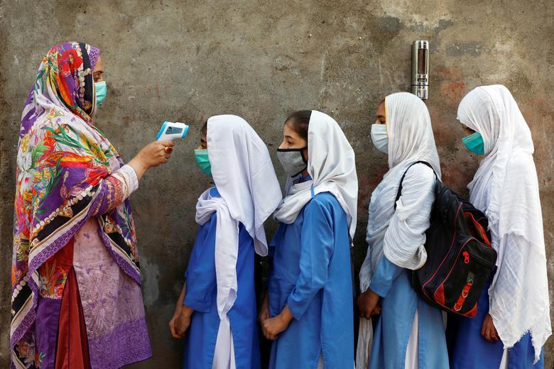 Οι μαθητές φορούν προστατευτικές μάσκες προσώπου καθώς ελέγχουν τη θερμοκρασία τους πριν μπουν σε μαθήματα στο Πεσαβάρ του Πακιστάν, Σεπτέμβριος 2020. REUTERS / Fayaz Aziz & nbsp;