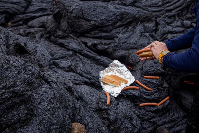 Мужчина готовит хот-доги на вулканическом участке на полуострове Рейкьянес после извержения вулкана в Исландии в пятницу 21 марта. REUTERS / Cat Gundry-Beck
