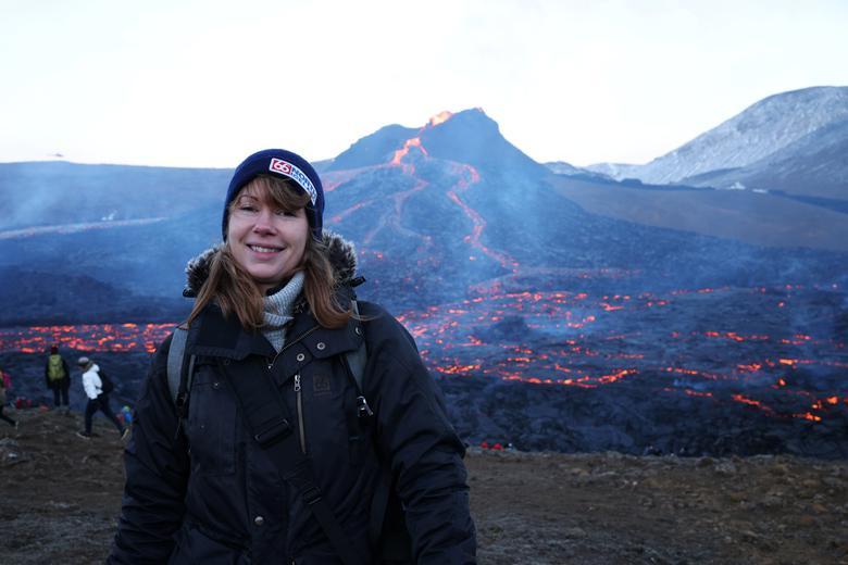 Турист позирует на вулканическом участке на полуострове Рейкьянес после недавнего извержения в Исландии, 26 марта 2021 года. REUTERS / Cat Gundry-Beck