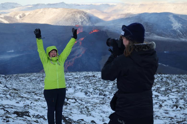 Туристы фотографируются на вулканическом участке на полуострове Рейкьянес после недавнего извержения в Исландии 26 марта 2021 года. REUTERS / Cat Gundry-Beck
