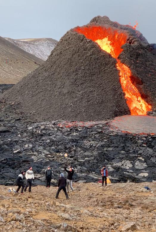 Люди играют в волейбол возле вулкана Фаградалсфьял, извергающего лаву, на полуострове Рейкьянес, Исландия, 27 марта 2021 года. Рут Эйнарсдоттир через REUTERS