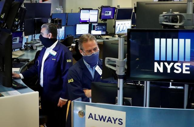 FILE PHOTO: Traders wearing masks work,on the floor at the New York Stock Exchange (NYSE) in New York, U.S., May 26, 2020. REUTERS/Brendan McDermid/File Photo