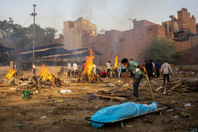 Bir adam, 22 Nisan'da Yeni Delhi'de bir krematoryum alanında koronavirüs nedeniyle ölen bir kişinin cesedini yakmak için bir cenaze töreni hazırlıyor.