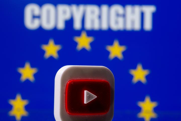 A 3D printed Youtube logo is seen in front of a displayed EU flag and...
