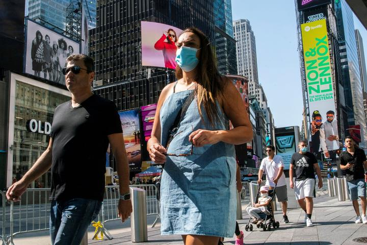 People wear masks around Times Square, as cases of the infectious...
