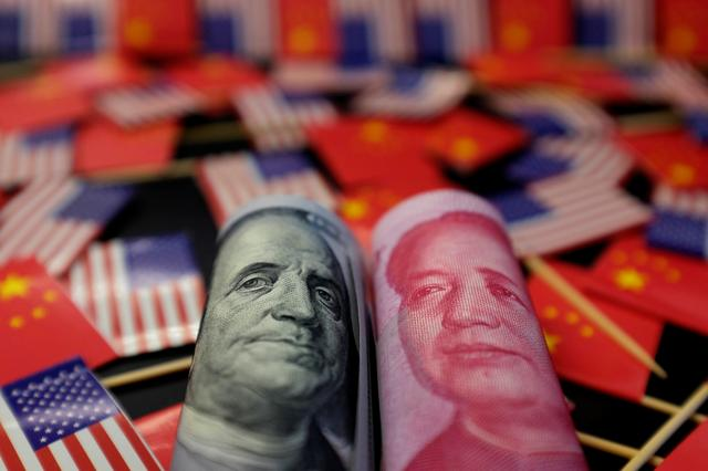 A U.S. dollar banknote featuring American founding father Benjamin Franklin and a China's yuan banknote featuring late Chinese chairman Mao Zedong are seen among U.S. and Chinese flags in this illustration picture taken May 20, 2019. REUTERS/Jason Lee/Illustration/Files