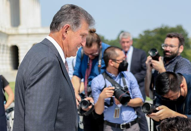 FILE PHOTO: U.S. Senator Joe Manchin (D-WV) walks past photographers as he leaves a 9/11 remembrance ceremony at the Capitol building in Washington, U.S., September 13, 2021. REUTERS/Evelyn Hockstein