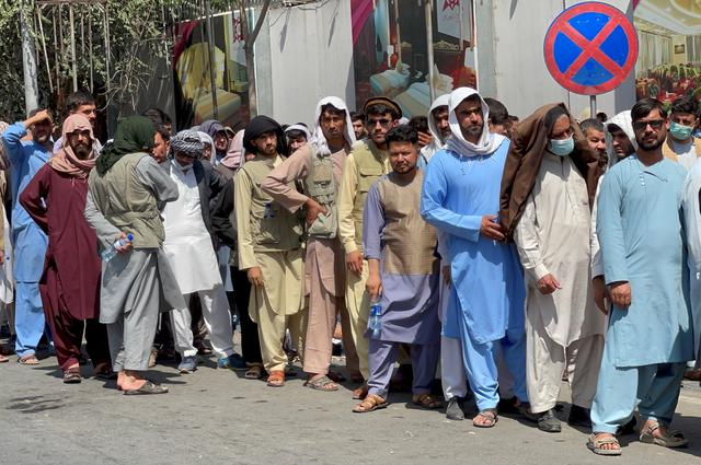 FILE PHOTO: Afghans line up outside a bank to take out their money after Taliban takeover in Kabul, Afghanistan September 1, 2021. REUTERS/Stringer/File Photo
