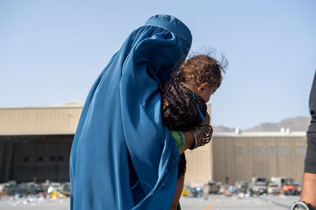 FILE PHOTO: A woman carries a child as passengers board a U.S. Air Force C-17 Globemaster III assigned to the 816th Expeditionary Airlift Squadron in support of the Afghanistan evacuation at Hamid Karzai International Airport in Kabul, Afghanistan, August 24, 2021. Picture taken August 24, 2021. U.S. Air Force/Master Sgt. Donald R. Allen/Handout via REUTERS