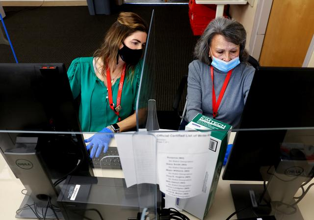Aimee Mac Ilory and Donna Young adjudicate a ballot that was rejected by a scanner at the Sacramento Registrar of Voters as California goes to the polls in a gubernatorial recall election allowing the voting public to remove current governor Gavin Newsom and replace him with one of 46 candidates, in Sacramento, California, U.S., September 14, 2021.  REUTERS/Fred Greaves