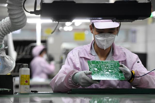 FILE PHOTO: An employee inspects a circuit board on the controller production line at a Gree factory, following the coronavirus disease (COVID-19) outbreak in Wuhan, Hubei province, China August 16, 2021. China Daily via REUTERS