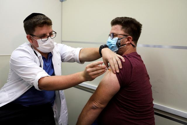 FILE PHOTO: An Israeli man receives a third shot of coronavirus disease (COVID-19) vaccine as country launches booster shots for over 40-year-olds, in Jerusalem August 20, 2021. REUTERS/Ammar Awad