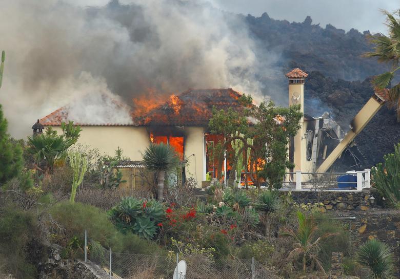 İspanya, La Palma'nın Kanarya Adası'ndaki Los Llanos de Aridane'deki Los Campitos yerleşim bölgesindeki Cumbre Vieja milli parkında bir yanardağın patlamasının ardından bir ev lav nedeniyle yanıyor, 20 Eylül 2021. REUTERS/Borja Suarez