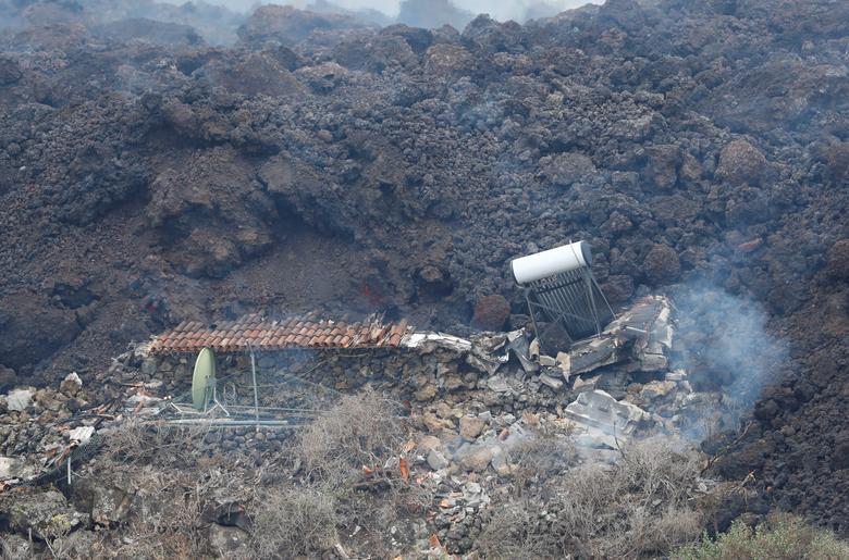 İspanya, La Palma'nın Kanarya Adası'ndaki Los Llanos de Aridane'deki Los Campitos yerleşim bölgesindeki Cumbre Vieja milli parkında bir yanardağın patlamasının ardından yıkılan bir evin arkasından lav akıyor, 20 Eylül 2021. REUTERS/Borja Suarez